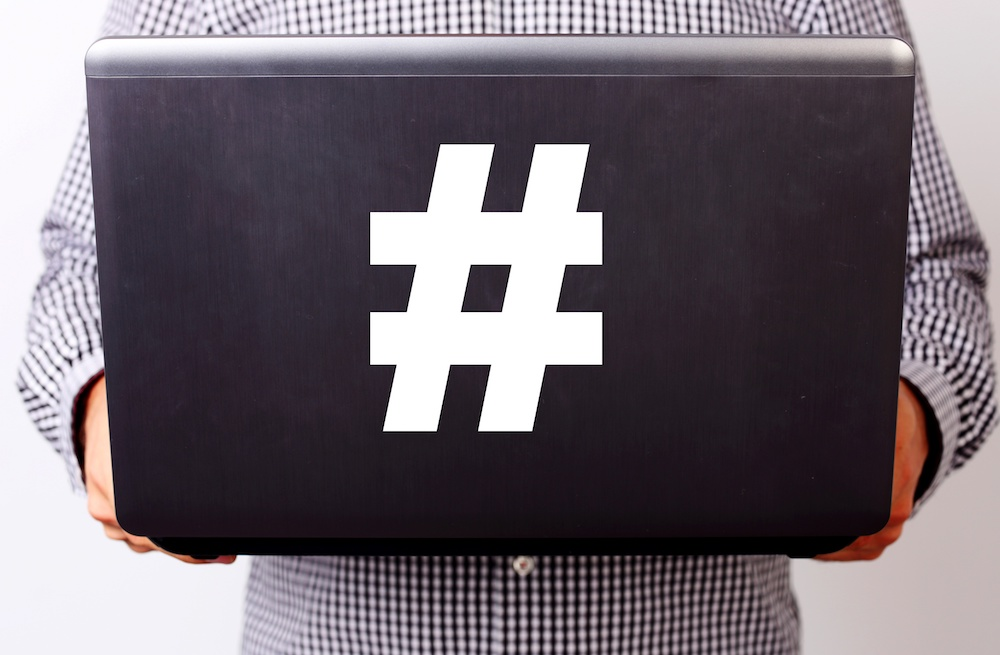 Closeup image of a man holding laptop with hashtag, from blog: 4 Types of Content Hashtags