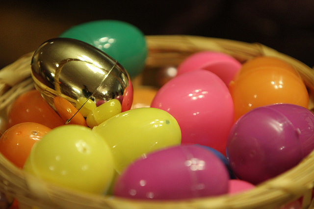 golden egg in a basket of pastel easter eggs