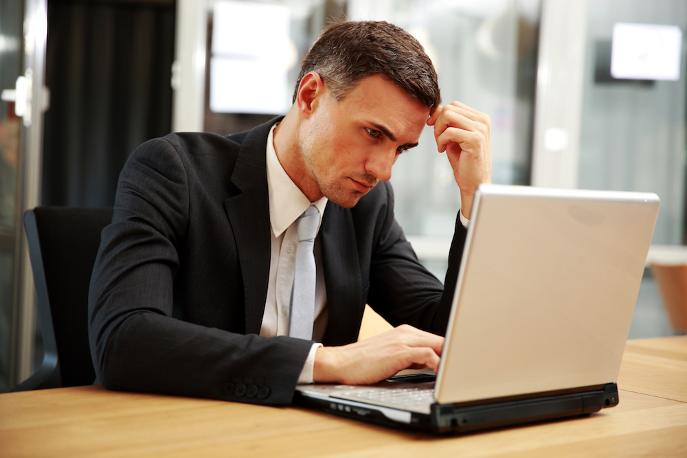 Confident businessman sitting with laptop at office Feeling Overwhelmed with Your Social Media Accounts?